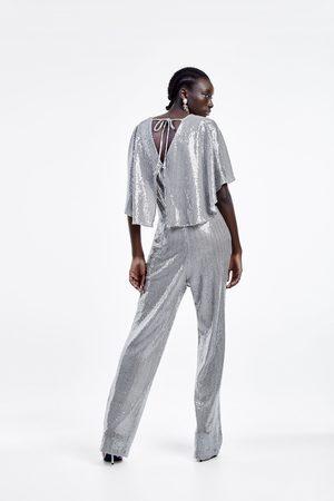 Zara Jumpsuit med capeäarmar och glans