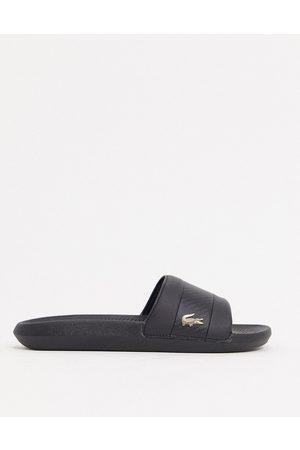 Lacoste – Svarta tofflor med guldfärgad krokodillogga