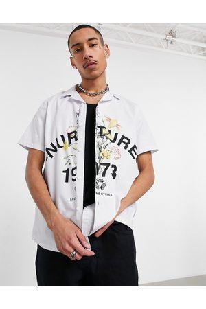 ASOS – Poplinskjorta i avslappnad passform med krage med slag och placerat blomtryck