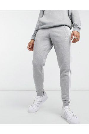 adidas – adicolor – Ljunggrå mjukisbyxor i skinny passform med tre ränder