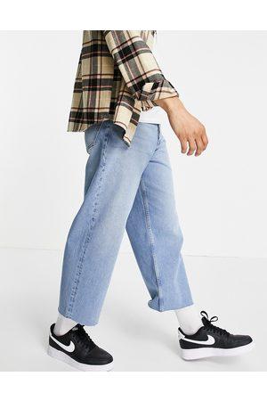ASOS – Mellanblå, vida, ankellånga jeans i 90-talstvätt med råskuren fåll