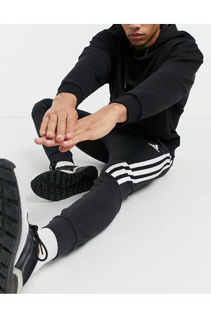 adidas Adidas – Svarta avsmalnande mjukisbyxor med tejpade detaljer i form av 3 ränder