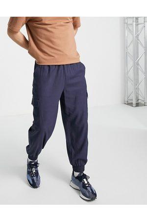 ASOS – Marinblå avsmalnande oversize-byxor i linnemix med cargofickor
